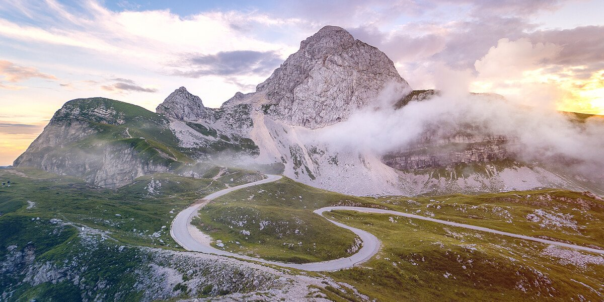 winding road rocky mountain rising background